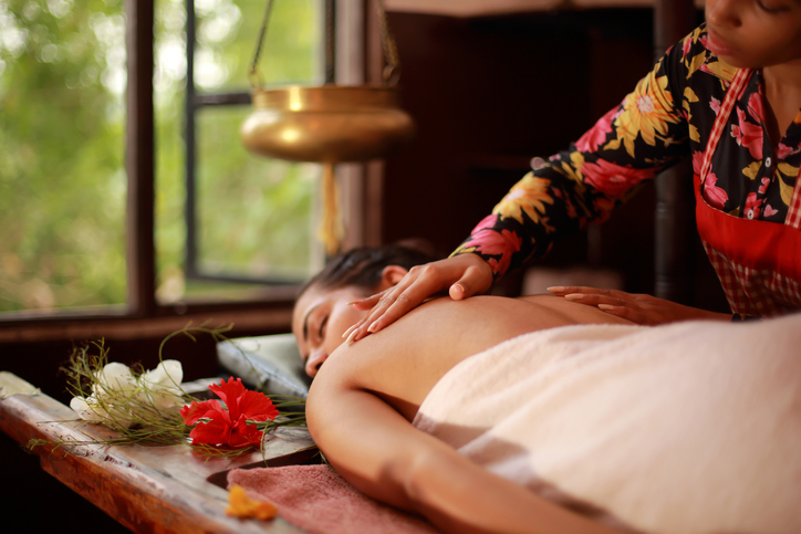 Female therapist massaging body in an ayurvedic spa following Indian traditional method.